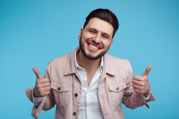 Выстрел в голову молодого мужчины в розовой стильной джинсовой куртке, улыбающегося и показывающего большой палец вверх на синем фоне