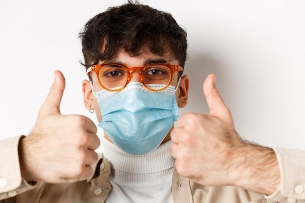 Выстрел в голову молодого человека в маске и очках, показывающего большие пальцы руки вверх, рекомендующего продукт, стоящего на белой стене. covid-19, концепция пандемии и социального дистанцирования.