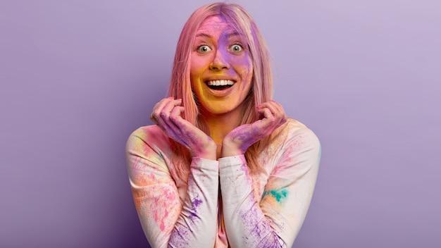 Il primo piano del volto di una donna allegra ottimista ha un ampio sorriso, tiene le mani vicino al viso, ha una faccia colorata sporca di colori holi, si prepara per la festa di primavera con soddisfazione e gioia