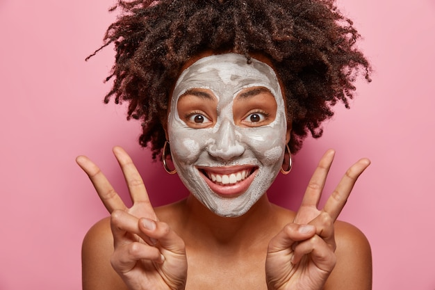 Headshot of optimistic woman has joy while applies clay mask, makes peace gesture with both hands with bare shoulders, wants to have fresh healthy skin, isolated over pink wall