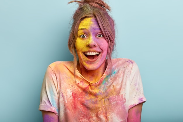 Headshot of optimistic woman plays with colors on holi festival, dressed in white t shirt