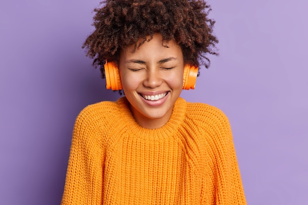 Headshot of overjoyed curly dark skinned teenage girl laughs positively closes eyes enjoys loud sound and favorite song in headphones wears casual jumper spends free time on listening music.