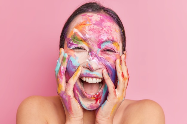 Headshot of overjoyed happy ethnic woman keeps hands on cheeks giggles positively keeps mouth opened has creative makeup smeared face with watercolor paints