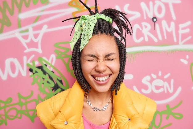 Headshot of overjoyed woman closes eyes smiles toothily has fun in urban place wears stylish clothes poses against street graffiti wall expresses positive emotions