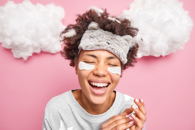 Headshot of overjoyed young woman laughs happily smiles broadly keeps eyes closed hears funny story from husband awakes in morning poses in nightwear with feathers in curly hair