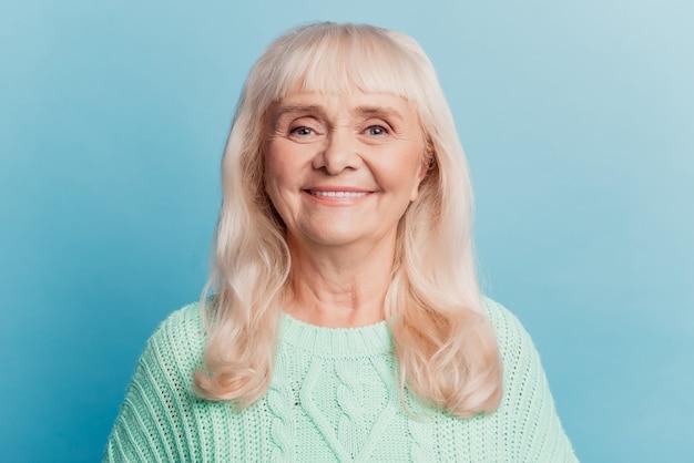 Фотография выстрела в голову счастливой старшей женщины, изолированной на синем фоне