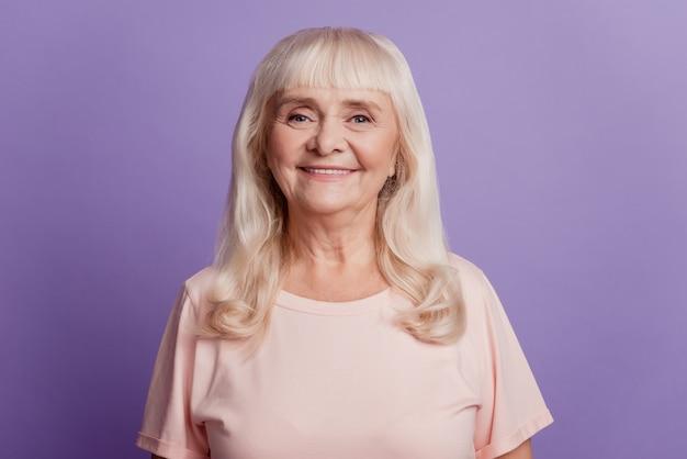 Фотография выстрела в голову счастливой старшей женщины, изолированной на фиолетовом фоне