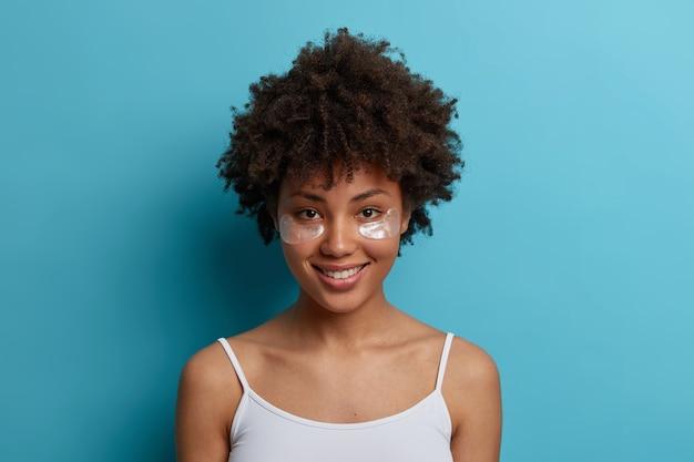 Colpo di testa di una donna afroamericana allegra dall'aspetto piacevole indossa cerotti idratanti sotto gli occhi, gode della procedura di cura della pelle, sorride delicatamente, pone