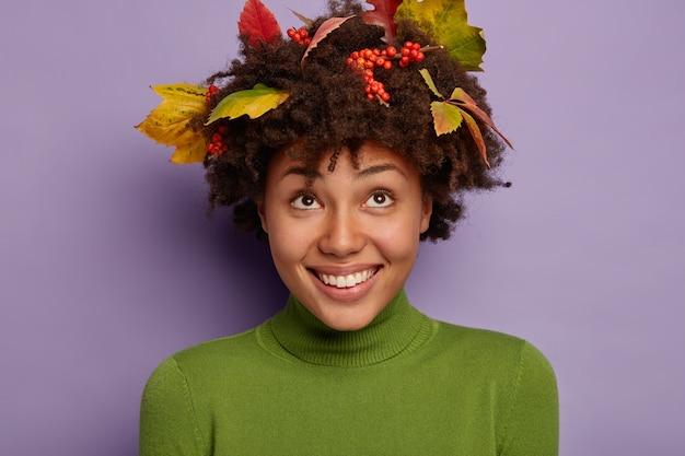 Il primo piano del volto di una donna allegra dall'aspetto piacevole ha un sorriso a trentadue denti, guarda sopra, si rallegra di avere una bella acconciatura decorata con foglie di autunno
