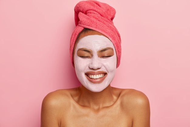 Il colpo alla testa di una donna dalla pelle scura dall'aspetto piacevole applica una maschera di fango sul viso, sta a spalle nude, ha procedure di bellezza, tiene gli occhi chiusi