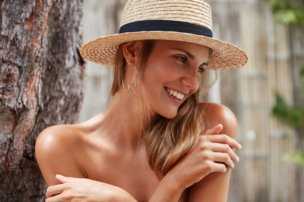 Headshot of pleasant looking happy young female model covers naked body with hands, wears summer hat, stands near exotic tree, looks positively away with dreamy expression, admires good rest