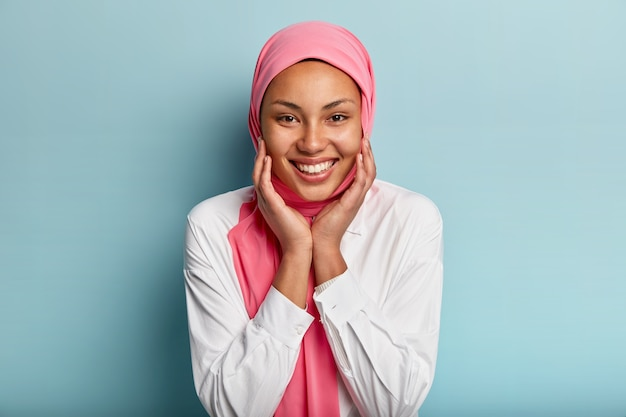 Headshot of pleasant looking muslim woman touches cheeks with both hands, shows white teeth, wears white shirt and pink veil, isolated against blue wall, expresses joy, happiness, delight