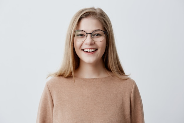 Headshot of pleasant-looking young caucasian woman wearing eyeglasses with broad smile showing her straight white teeth being happy because of positive news. blonde girl with pleasant smile