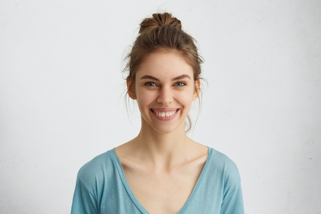 Headshot of pleasant-looking young caucasian woman with broad smile showing her straight white teeth being happy