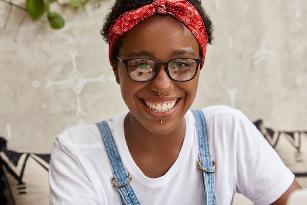 Il primo piano del volto di una giovane donna dall'aspetto piacevole ha un sorriso brillante, indossa il piercing al naso e alle labbra