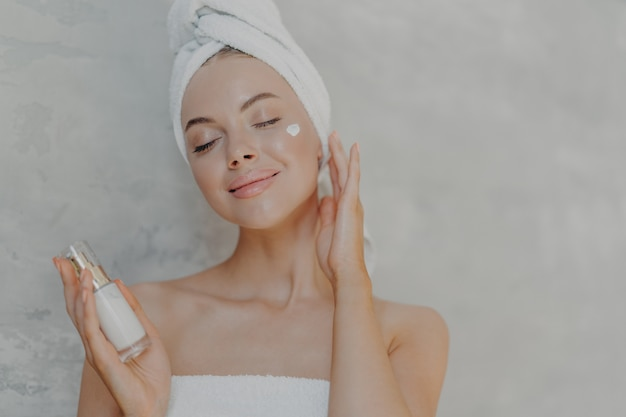 Headshot of pleased attractive woman applies face lotion satisfied with new cosmetic product