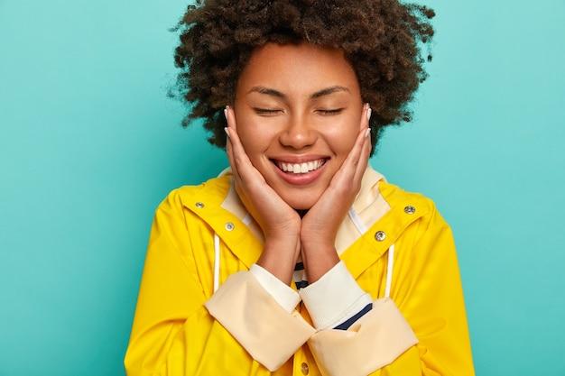 Headshot di donna afroamericana allegra felice tocca le guance, chiude gli occhi, gode di un momento piacevole, indossa un impermeabile giallo, isolato su sfondo blu.