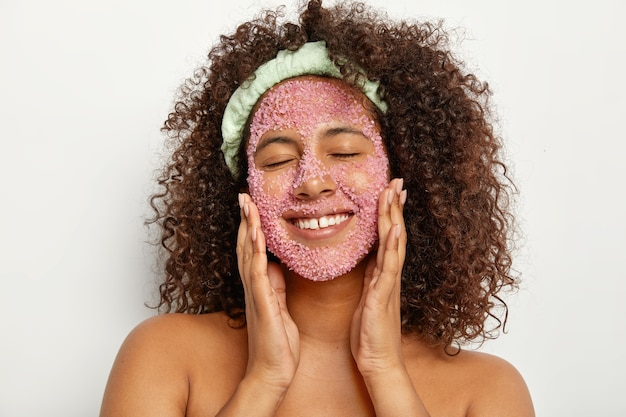 Headshot of pleased relieved woman massages face with sea salt, smiles happily, keeps eyes shut gets facial treatment for smooth soft skin reduces dark dots wears headband on head, has well cared body