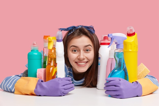 Headshot of pleased smiling woman, friendly look, embraces bottles with detergent, wears gloves, washes dish, cleans kitchen