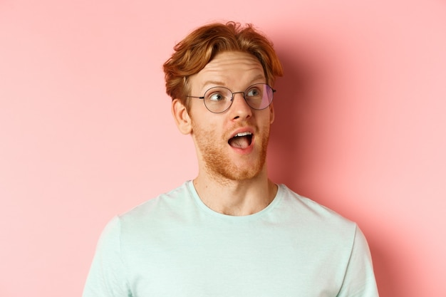Headshot portrait of amazed redhead man in glasses, open mouth and gasping, looking at upper right corner banner or logo, standing over pink background.