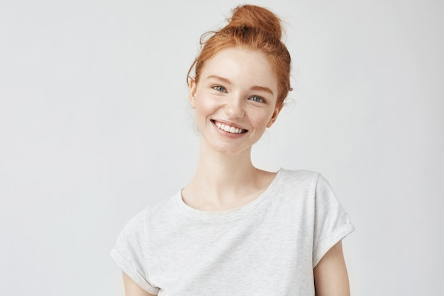 Headshot portrait of happy ginger woman with freckles smiling white.