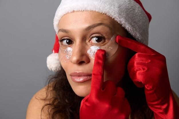 灰色の背景に分離された、カメラを注意深く見ている眼帯を身に着けているサンタ帽子の美しいブルネットの女性のヘッドショットの肖像画。美容美容院のクリスマス広告のスキンケアコンセプト