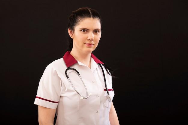 Выстрел в голову портрет медсестры в униформе со стетоскопом, изолированные на темном фоне, копией пространства