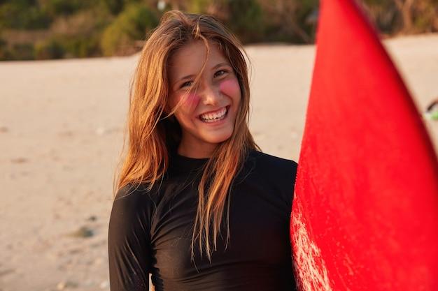 Headshot di surfista caucasico positivo in muta nera, ha un sorriso a trentadue denti sul viso
