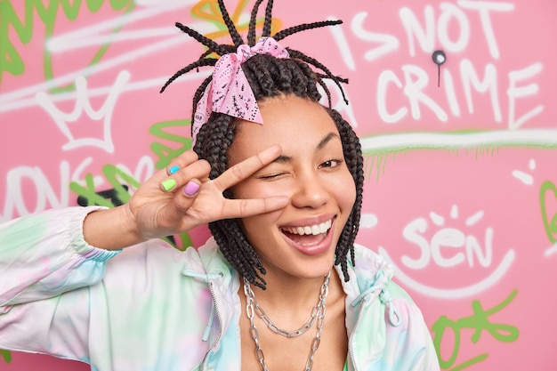 Headshot of positive cool hipster girl makes peace gesture over eye smiles broadly and winks eye dressed in fashionable clothes poses against colorful graffiti wall