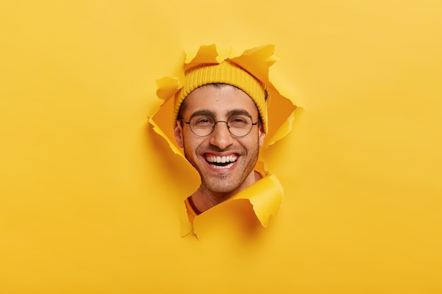 Headshot of positive unshaven young man smiles broadly, wears round optical glasses, yellow headgear