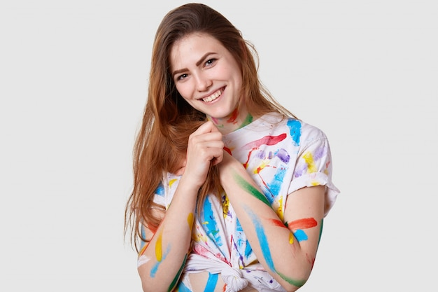 Headshot of positive young female model keeps hands together, smiles gently, wears casual stained t shirt, enjoys painting