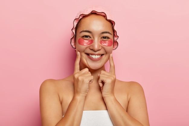 Primo piano del volto di una donna piuttosto bella sorride positivamente, tiene gli indici sulle guance, gode della morbidezza della pelle, indossa cerotti di collagene sotto gli occhi per ridurre le linee sottili, sta mezzo nudo al coperto