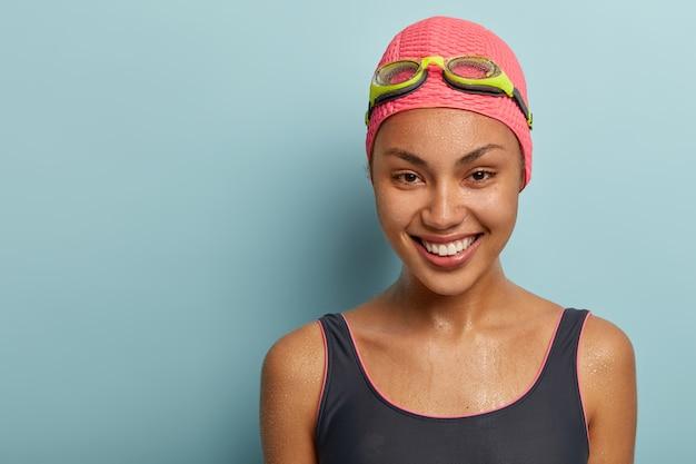 Headshot del nuotatore abbastanza femminile che posa con gli occhiali di protezione