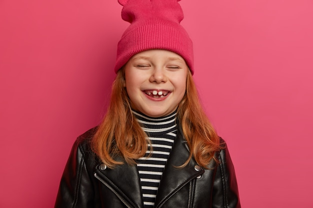 Headshot of pretty ginger girl has playful upbeat expression, closes eyes and laughs out happily, has positive smile, rejoices having two adult teeth, going to attend dentist, isolated on pink wall