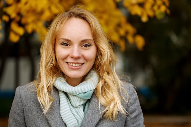 Headshot of pretty smiling blonde woman at the autumn nature with copy space looking at camera