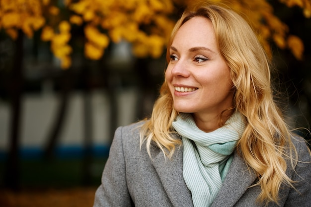 Headshot of pretty smiling blonde woman at the autumn nature