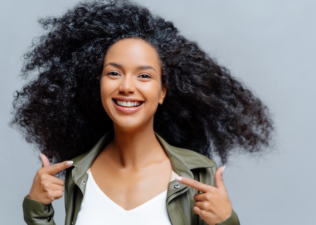 Headshot of pretty smiling woman with afro hairstyle, points both index fingers at herself, feels proud of herself, wears leather shirt, isolated