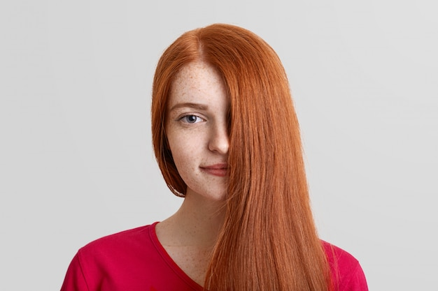 Headshot of pretty young ginger female model covers half of face with her straight luxurious hair