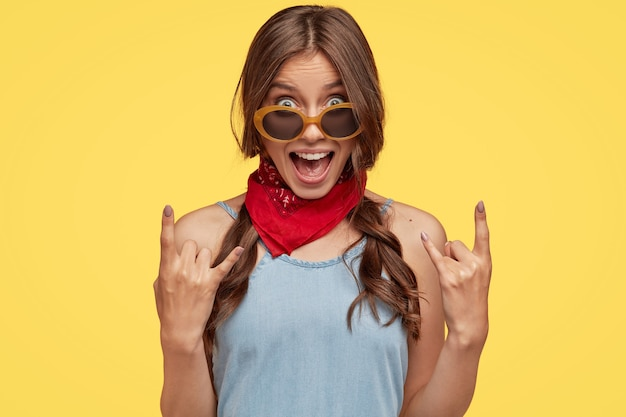 Headshot of provocative cool female hipster shows rock n roll hand gesture, exclaims something loudly