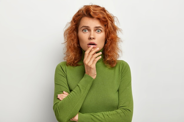 Headshot of puzzled emotive woman keeps hand near opened mouth, has scared look
