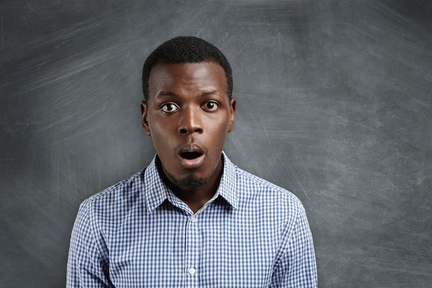 Headshot of puzzled or suprised african employee dressed in checkered shirt looking in shock and frustration against blank chalkboard with copy space for your text or advertising content