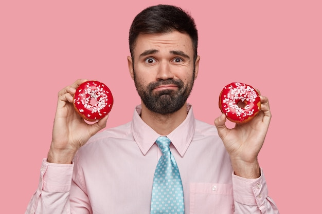 Headshot of puzzled unshaven man dressed formally, holds two doughnuts in both hands