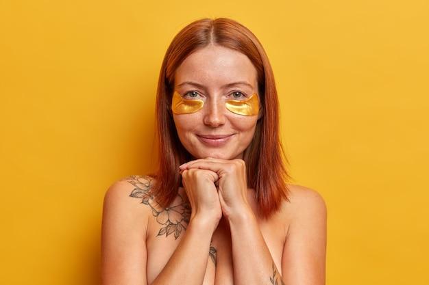 Primo piano del volto di donna rossa con acconciatura bob, gode di procedure di bellezza, applica macchie di collagene d'oro, sta con il corpo nudo al coperto, si preoccupa della pelle e dell'aspetto, isolato sul muro giallo