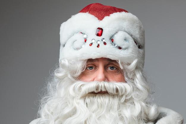Primo piano del volto di babbo natale con cappello rosso, uomo stanco con i capelli grigi