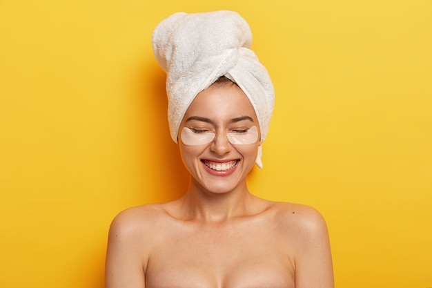 Headshot of satisfied beautiful naked woman applies white patches under eyes to reduce dryness, has pampering session, plumps up skin, wears white towel on head after shower