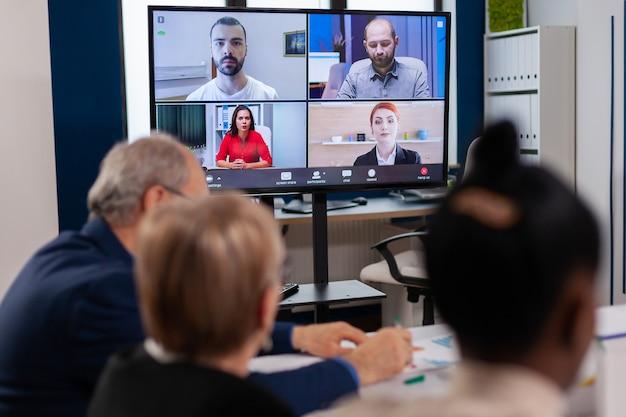 ビデオ通話のブレインストーミングで話しているリモートの多民族の従業員のヘッドショット画面アプリケーションビュー