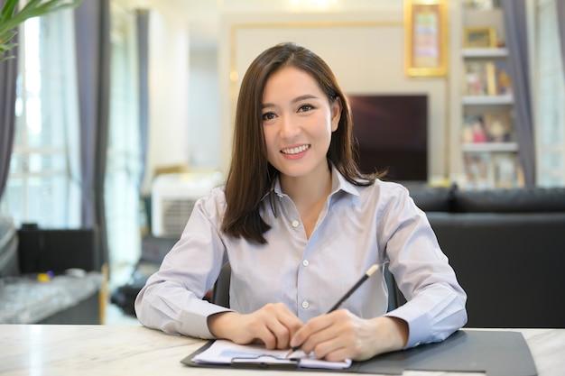若いアジア女性実業家のヘッドショットスクリーンビューは、自宅からパートナーまたはビジネス同僚とのビデオ会議を使用してオンラインになっています。