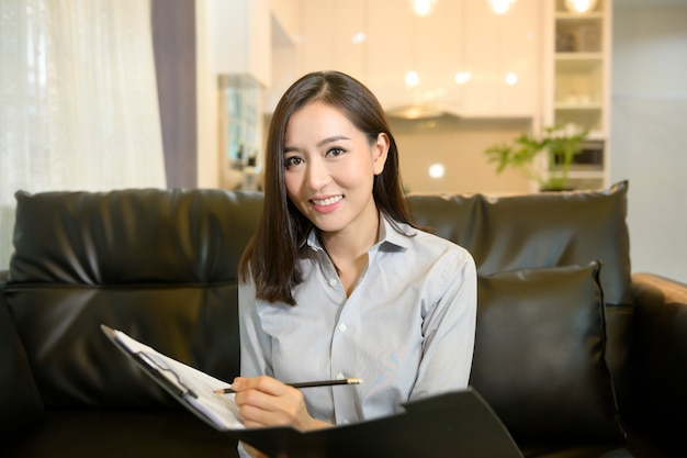 Headshot screen view of young asian businesswoman is online using video conference with partners or business coworkers  from her home .