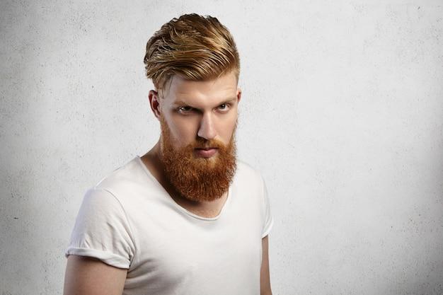 Primo piano del volto di hipster barbuto sicuro di sé con taglio di capelli alla moda e corporatura muscolare che indossa la maglietta con maniche arrotolate guardando con espressione severa, arrabbiato con qualcosa.
