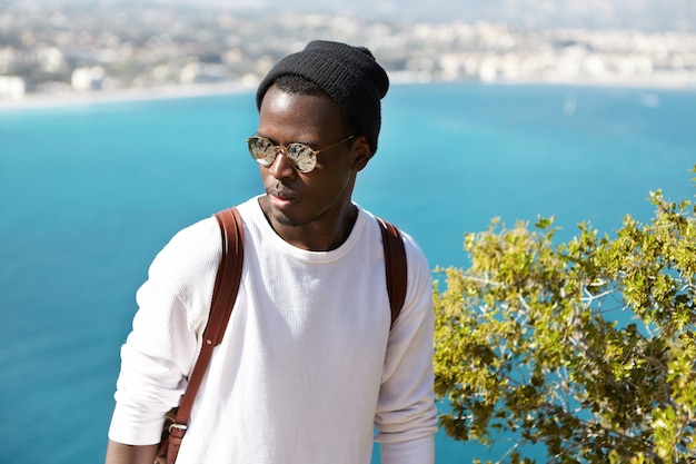 Headshot of serious african man against picturesque view of european seaport town. traveler in stylish clothing and sunglasses looking pensive and puzzled thinking about overnight stop